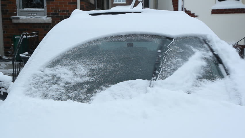 Winter wipers clearing snow. Starting a snow covered car. Toronto, Ontario, Canada.