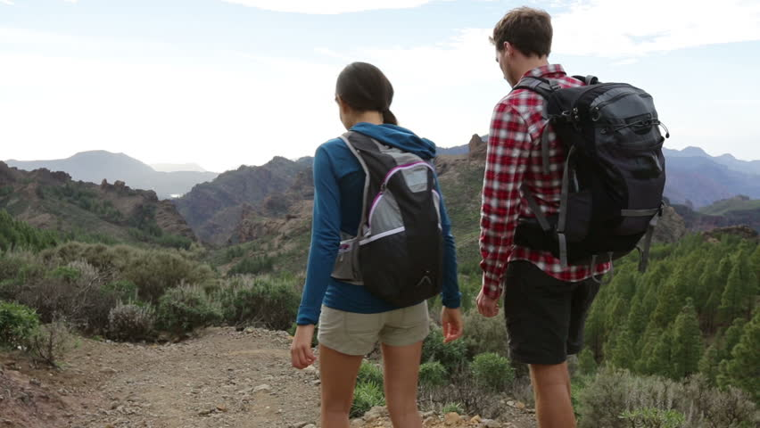 Hiking couple walking in mountain forest. Hikers walking on hike path in woods outdoors. Young active couple on trail to Roque Nublo, Gran Canaria, Canary Islands, Spain. | Shutterstock HD Video #5837936
