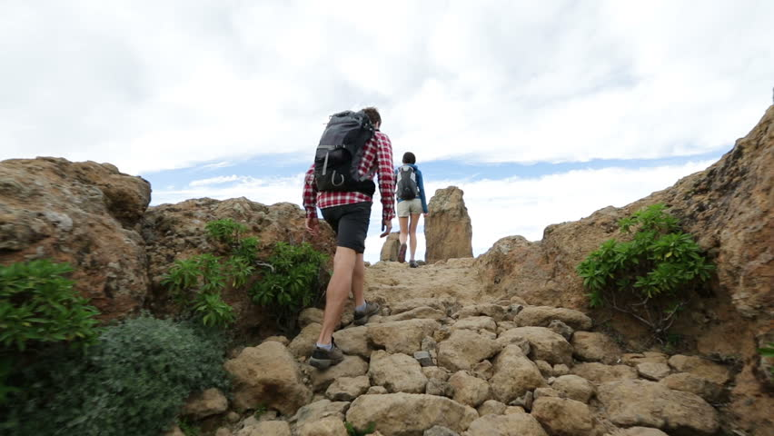 Hikers reaching summit top after ascent. Hiking couple walking outdoors wearing hiker backpacks. Woman and man hiker on trail to Roque Nublo, Gran Canaria, Canary Islands, Spain. | Shutterstock HD Video #5838086