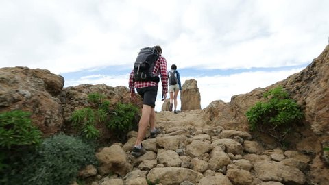 Hikers reaching summit top after ascent. Hiking couple walking outdoors wearing hiker backpacks. Woman and man hiker on trail to Roque Nublo, Gran Canaria, Canary Islands, Spain.