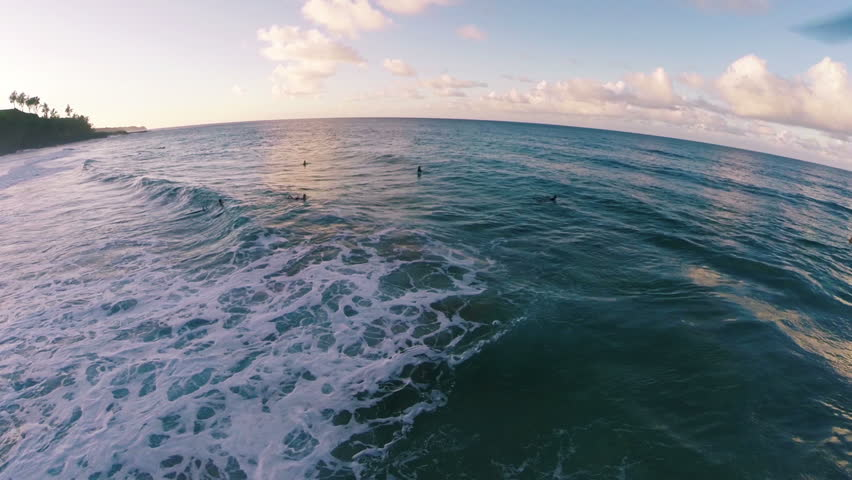 Aerial Slow Motion Shot of Surfers Paddling out During a Perfect Sunset on a Secret Beach in Kauai Hawaii - HD 1080 Video in Slow Motion with Golden Water Low Flying Pan Over the Ocean