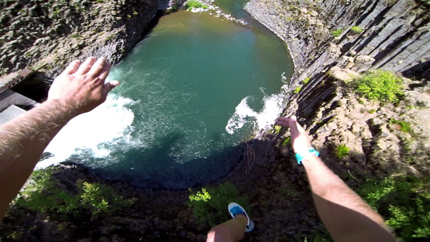 Extremely High POV Cliff Jump into Water above a Waterfall Trees and Rocks Below on a Beautiful Sunny Day in Summer in the Forest with a Thumbs Up to Bystanders Extreme Fun Point of View Head Camera #5882156