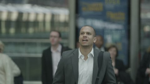 Stressed businessman at railway station runs to try and catch his train in time. In slow motion.