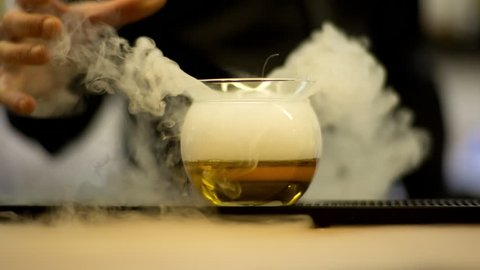 an experimental cocktail waiter makes a special drink with dry ice smoke in a bar