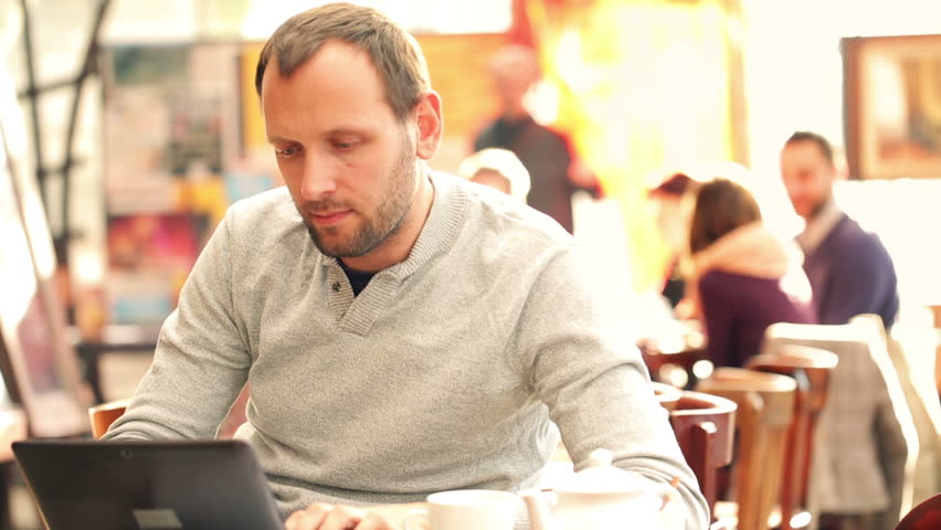 Man with modern laptop drinking tea in cafe