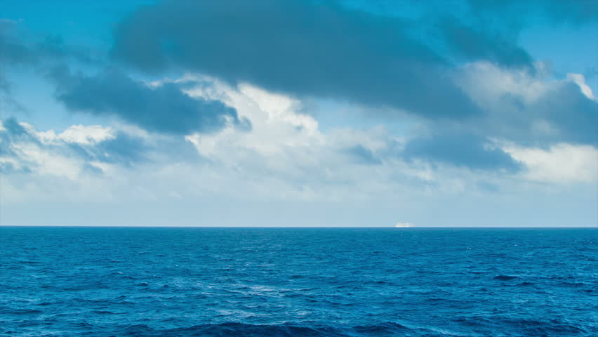 A Majestic Long Range Seascape with a Cruise Ship on the Horizon and Thunderous Clouds in a Blue Sky.