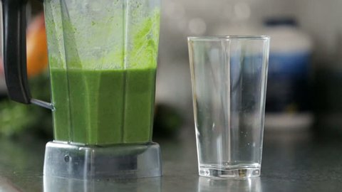 Slow motion pouring a healthy, green smoothie made of blended fruits and vegetables.