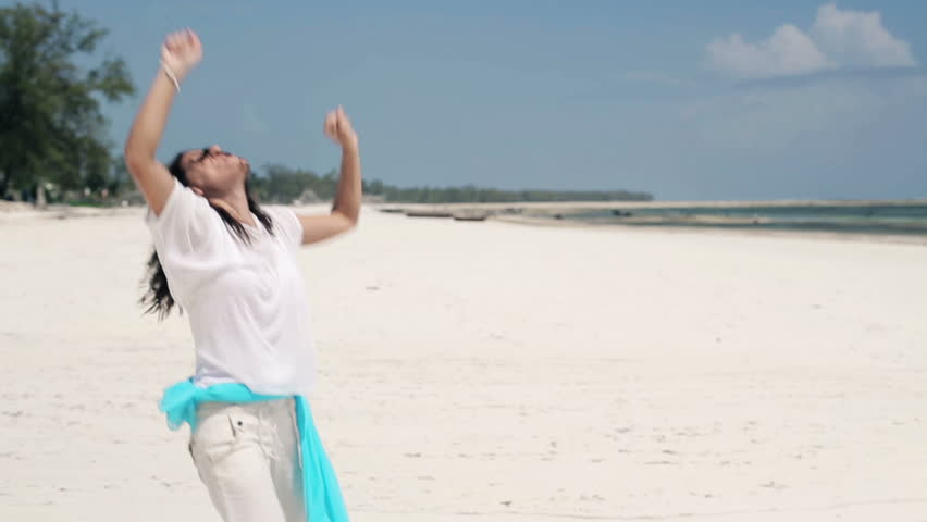 Happy young woman playing, having fun on exotic beach