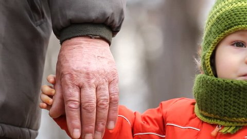 Cute grandson hold grandfather hand, simple approach gesture, overcome gap