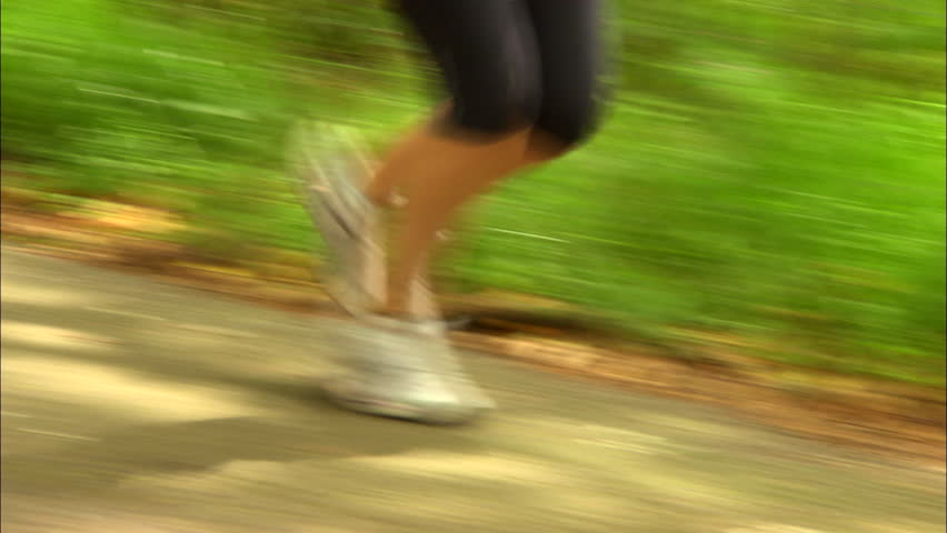 Close shot of woman's legs running down country lane