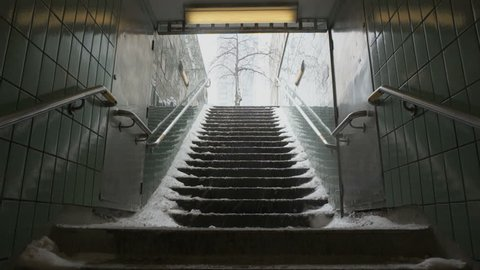 Snow filled staircase leading up out of the underground subway pedestrian tunnel, into the daylight