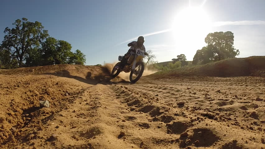 MOTOCROSS MOTORCYCLE RIDER IN BACK-LITE LIGHT AT SUNSET THROWS DUST IN AIR WHILE IN EXTREME SLOW MOTION  HIGH DEFINITION STOCK VIDEO FOOTAGE HD