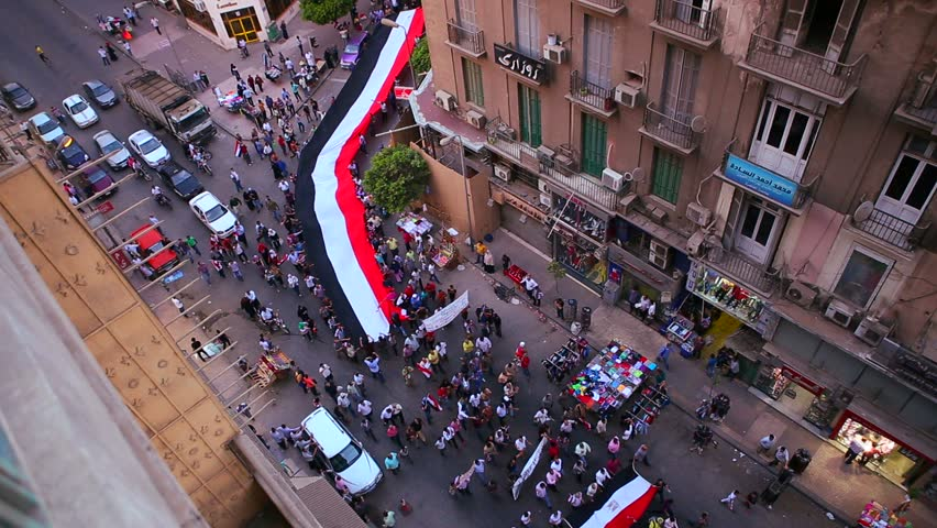 View from overhead looking straight down as protestors carrying banners round a corner and pass through and intersection in the streets of Cairo, Egypt.