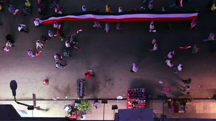 View from overhead looking straight down on protestors carry a banner and march in the streets of Cairo, Egypt at night.