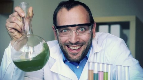 Crazy, mad scientist laughing in laboratory