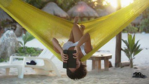 Hispanic woman reading e-book in hammock on caribbean beach at Mahahual, Quintana roo, Mexico