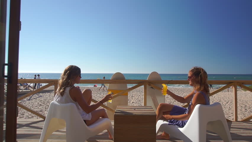 Young women sitting in a beachfront bar with ocean view and sipping cold drinks on a beautiful sunny day in hot summer. Surfer girl friends have a refreshing drink in beach bar after surfing