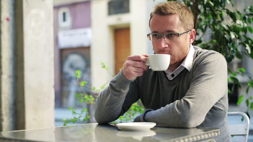 Man drinking coffee in street restaurant and relaxing.  | Shutterstock HD Video #6081386