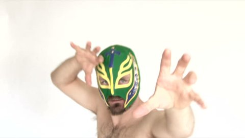 Model released man in studio wearing various lucha libre masks wrestles camera.