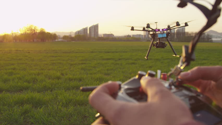 SLOW MOTION CLOSEUP: Drone operator holding a transmitter