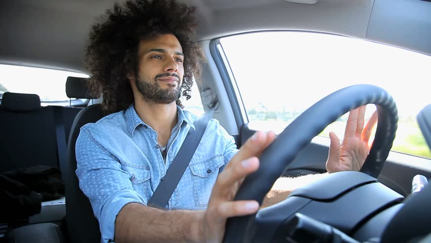 Cool man listening music while driving car traveling