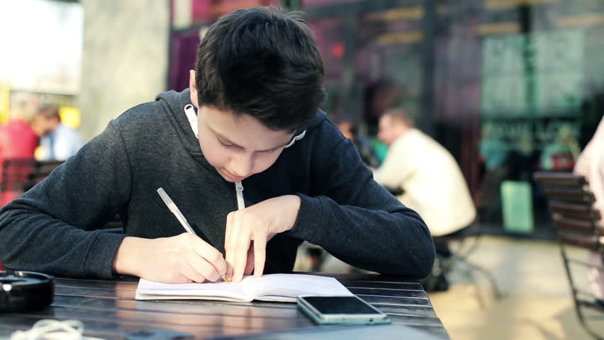 Teenager doing homework, calculating math on smartphone in cafe