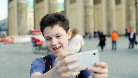 Young teenager taking selfie photo with his smartphone by Brandenburg gate