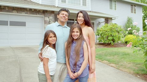 Tilt up of a hispanic family standing in their driveway and then turning around to walk back into the house