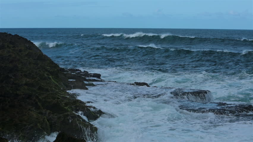 Beautiful rough surf on jagged rock ocean shore. Rough Caribbean and Atlantic Ocean waves and surf surging against rugged rocky coast. Beautiful blue water splash with white foam.