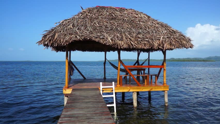 Tropical Hut On Stilts Over Water With Thatched Roof Made Of Dried Palm Leaves Caribbean