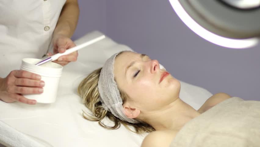 spa, beautiful woman making a facial mask