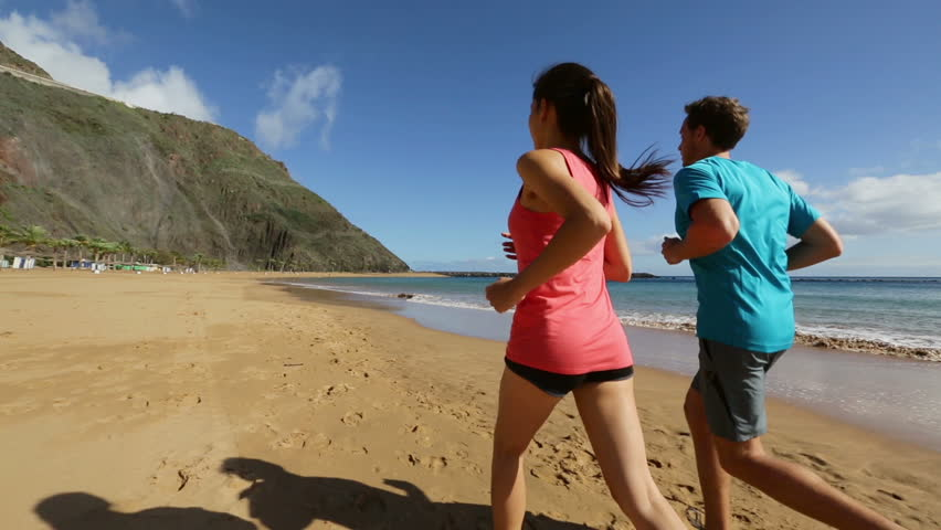 Runners Jogging On Beach Training Together Man And Woman Joggers Exercising Outdoors