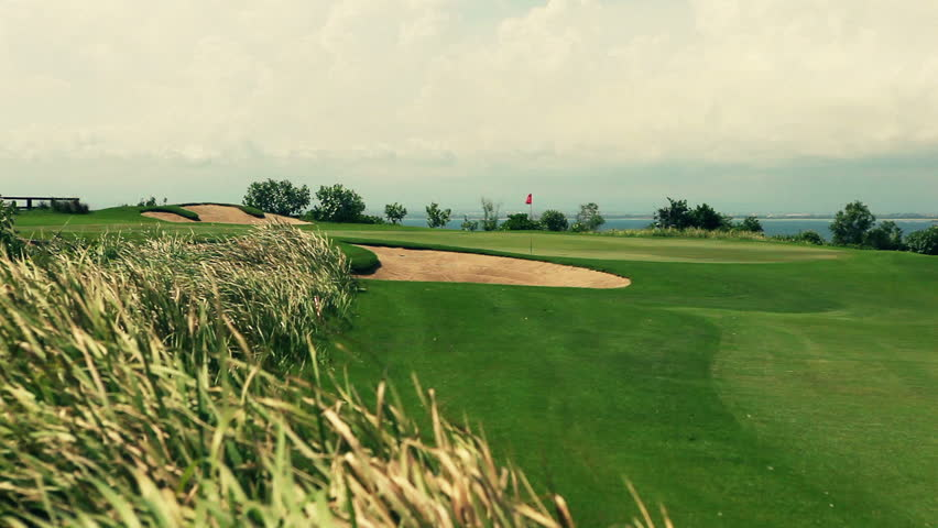 Wide angle panorama of a beautiful golf course with grass moving gently in the
