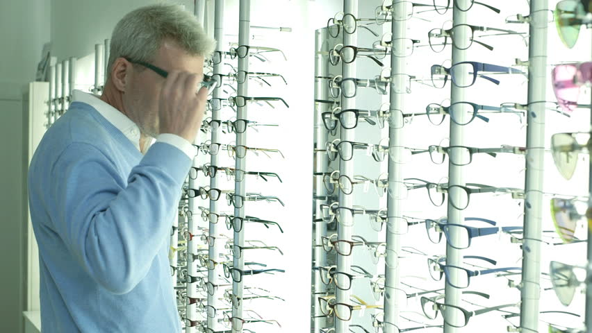 Male customer browses Optician shop and selects glasses to try on