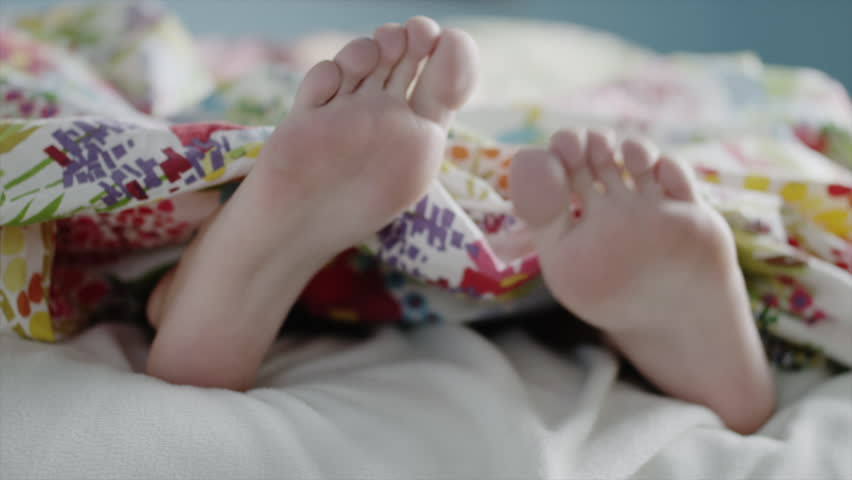 Close up of teenage girls feet dancing under blanket