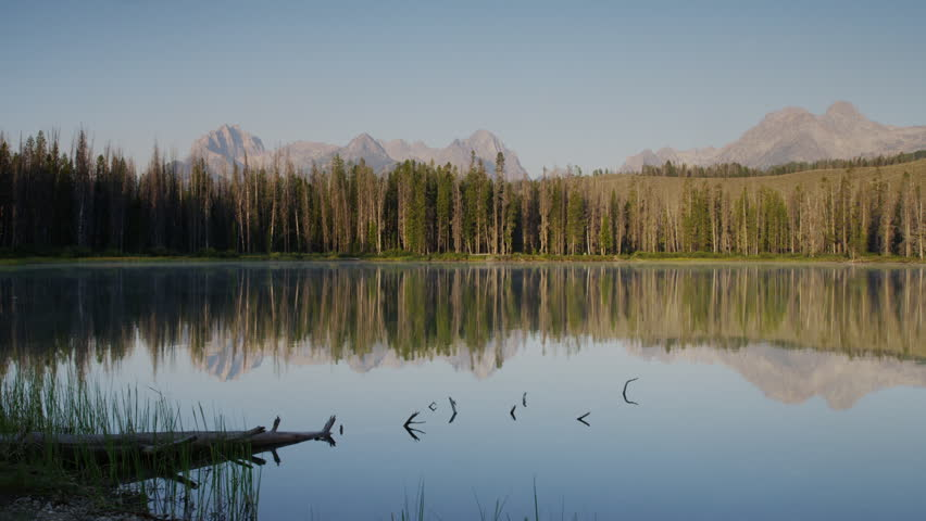 Wide shot scenic view of mountains and calm lake / Redfish Lake, Idaho, United States