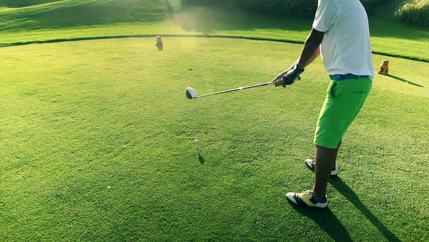 Close up of golfer teeing off on a beautiful golf course during sunset