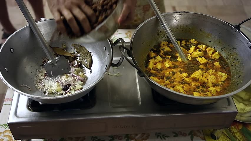 Local cuisine & technique demonstrated by Indian woman in New Delhi, India. Here a chickpea & paneer dish is prepared. Paneer is cottage / farmer's cheese - makes up large part of vegetarian meals.