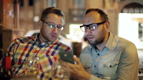 Two guys with smartphone talking in the restaurant at night, steadycam shot