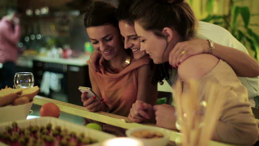 Happy women using smartphone on a party with man background.