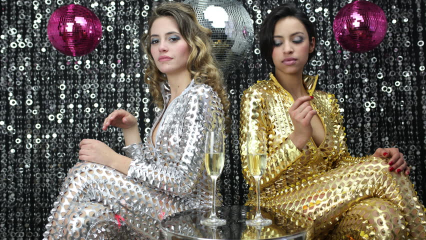 4k stopmotion of two beautiful sexy disco women in gold and silver catsuits, in a bar lounge setting. Useful for fashion, beauty, music and events
