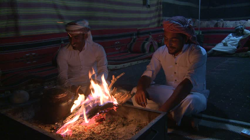 WADI RUM, JORDAN CIRCA 2013 - Two Bedouin men sit in a tent in front of a campfire in the desert and laugh and talk.