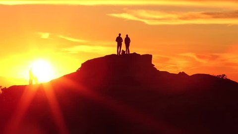 Mountain Sunset Pan HD video with silhouettes of people standing on the top of a peak.
