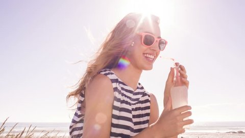 Smiling girl with lemonade at the beach on sunny summer day