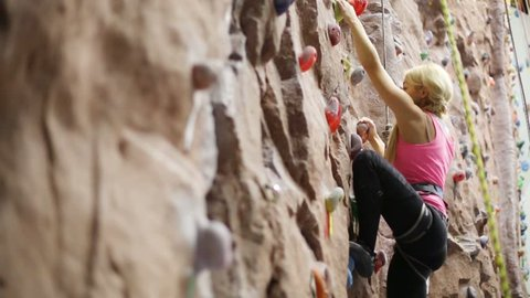 Pretty blonde woman with special equipment climbs on wall