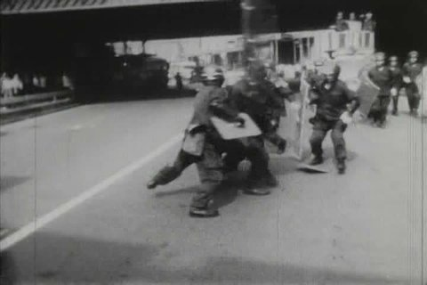 CIRCA 1970s - 1970s black and white footage of students protesting and being attacked by police in Tokyo, Japan