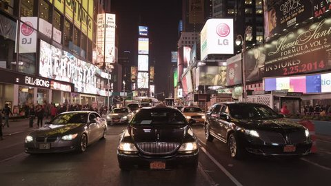 NEW YORK - APRIL 17, 2014: Uber car driving through beautiful Times Square at night in slow motion in 4K in New York. Times Square is an intersection and neighborhood in Midtown Manhattan, NYC, USA.