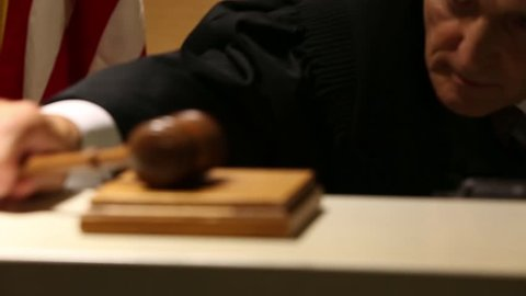 Judge pounds gavel, close up
