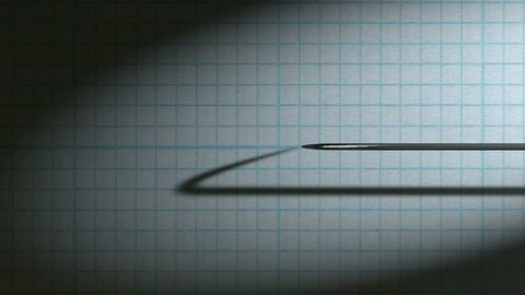A closeup view closeup pan of a polygraph lie detector test needle drawing a red line on graph paper