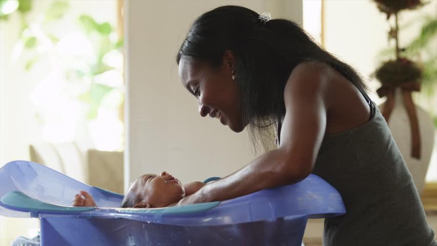 Medium Shot Woman washing baby boy (2-5 months) in bathtub